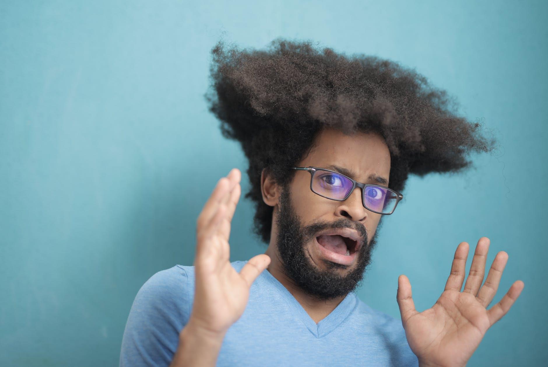 man in teal v neck shirt wearing black framed eyeglasses